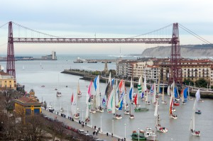 PORTUGALETE, SPAIN - DECEMBER 21, 2013: Championship of sailboats under the hanging bridge in Portugalete.